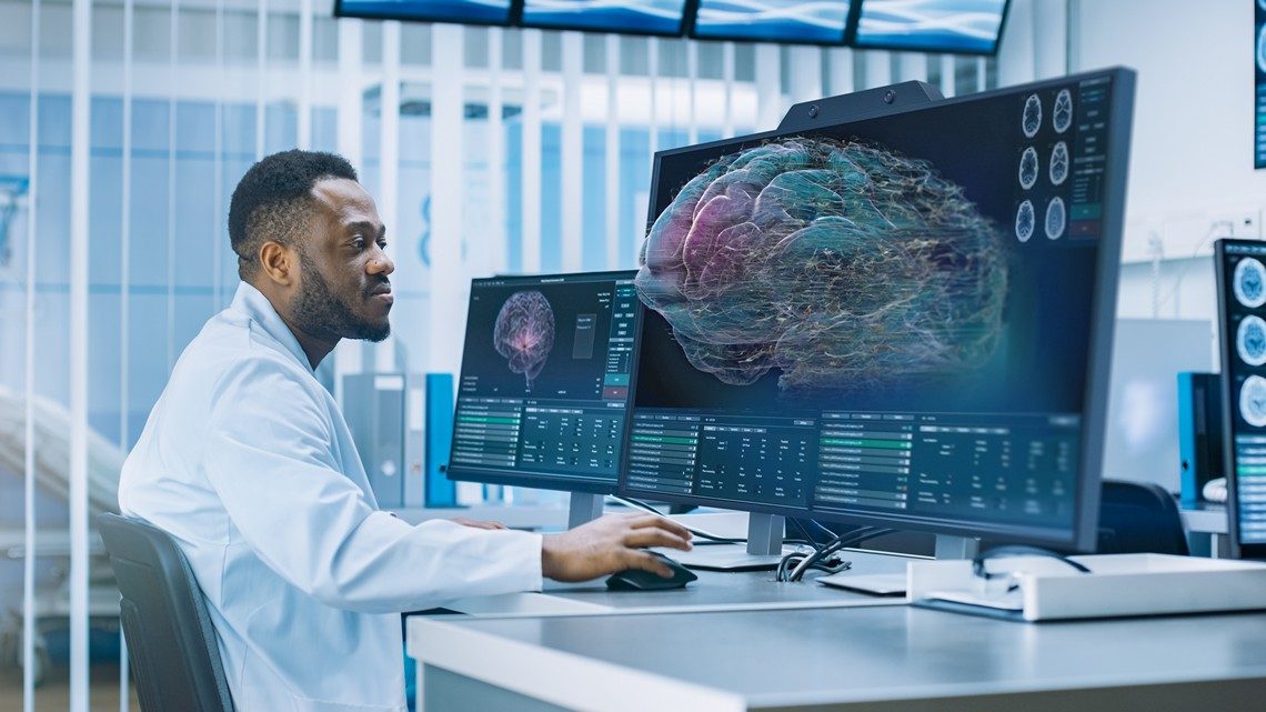 Medical doctor sits at his desk and uses the mouse to operate the interactive 3D scan of a brain on the glasses-free 3D display ZVIEW by United Screens