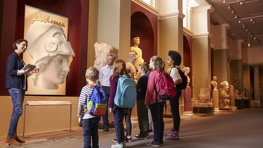 "A group of children with their teacher looking at a 3D statue on a ZBOX 85"" Portrait AS3D display in a museum."